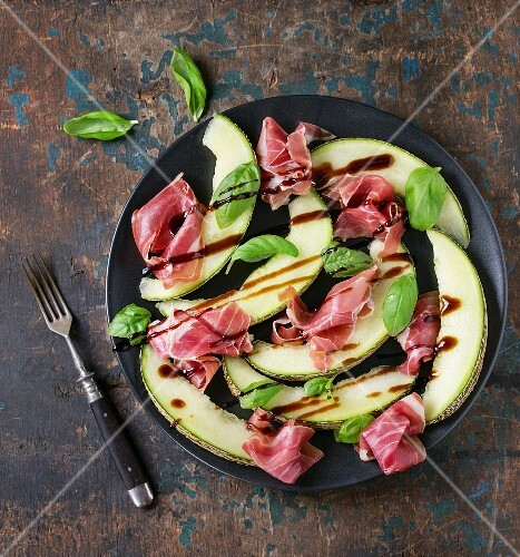 Sliced melon with ham and basil leaves, served on black ceramic plate