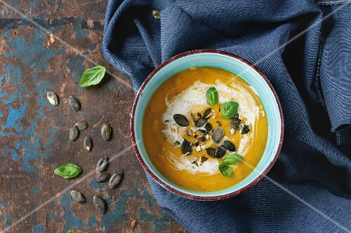 Turquoise ceramic bowl of pumpkin and sweet potato cream soup with fresh basil, cream and seeds