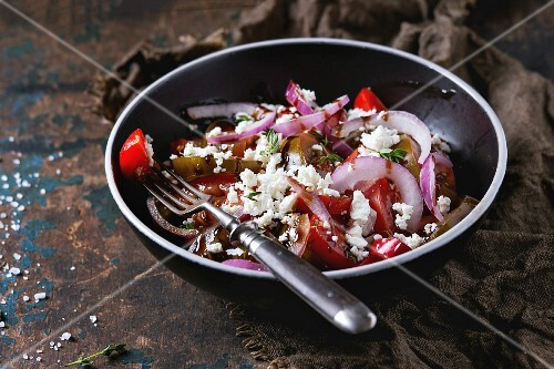 Black bowl with sliced different tomatoes, red onion, balsamic sause, thyme and feta cheese salad