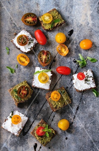 Small rye sandwiches with cherry tomatoes, ricotta cheese and pesto sauce, served with fresh herbs and balsamic sauce