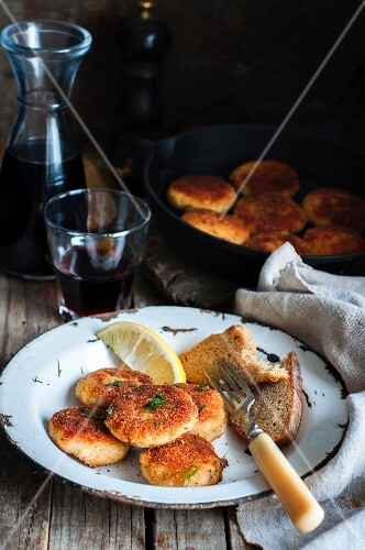Fishcakes in breadcrumbs with a slice of bread and lemon