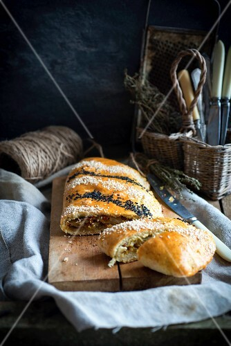 Bread stuffed with cabbage and topped with sesame seeds on a chopping board