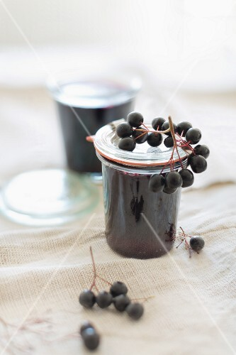 Home-made aronia berry jelly in glass jars with fresh aronia berries