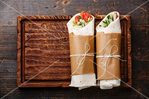 Tortilla wraps sandwiches with fresh vegetables on wooden cutting board