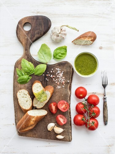 Homemade pesto sauce, fresh bread, cherry tomatoes on wooden cutting board