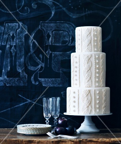 A white three-tiered wedding cake with a plaited pattern in front pf a blue background