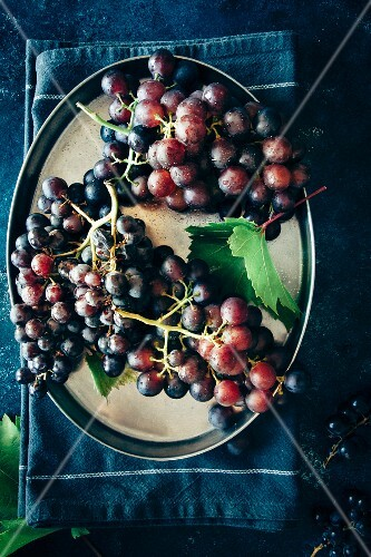 Red grapes with a leaf on a tray