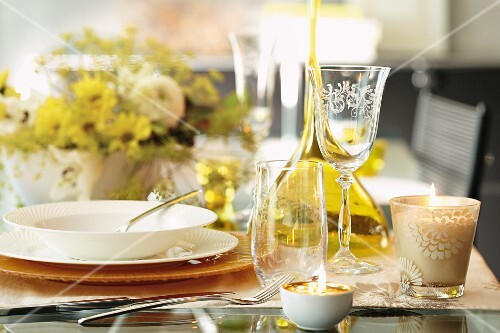 An autumnal set table with glasses, candles and a bouquet of flowers