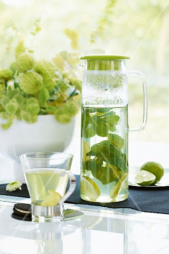 Hot lemonade with mint in a glass jug and tea glass
