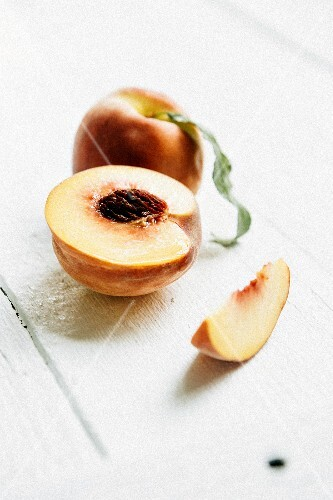Whole and sliced peaches on white wood