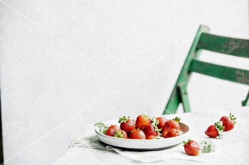 A table scene with strawberries and a green chair