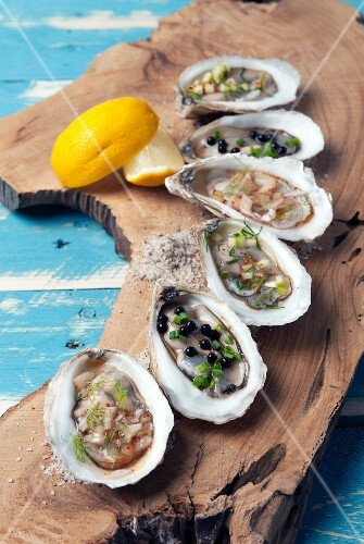 Assorted oysters on a plank of wood
