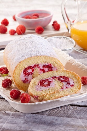 A Swiss roll with raspberries and icing sugar