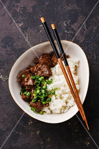 Slow cooked Beef with Rice and green onions in bowl