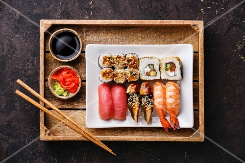 Sushi Set nigiri and rolls with chopsticks, ginger, soy sauce and wasabi in tray on dark background