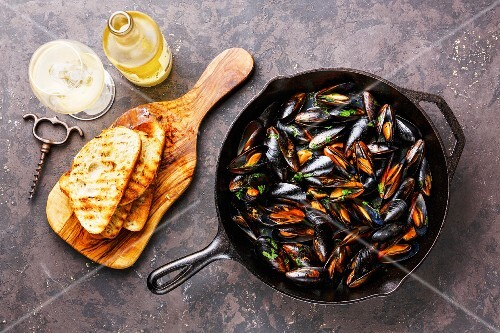 Mussels on frying pan, Bread toasts and Wine on dark background