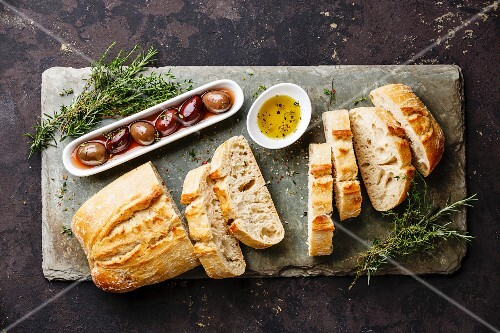 Fresh Ciabatta bread cut in slices on stone slate board with olives, oil and herbs on dark background