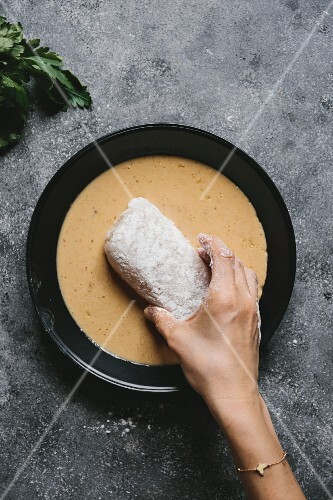 A woman is dipping flour coated fish fillet into an egg mixture