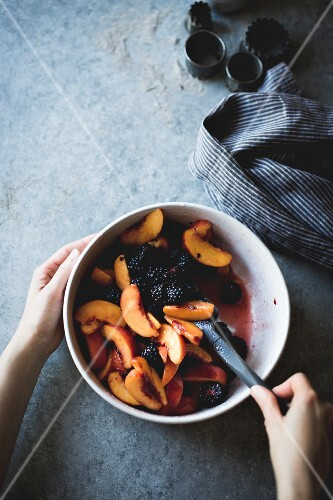 Mixing peaches and blackberries in a mixing bowl