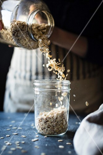 A woman pouring oats it to a jar