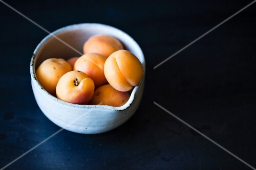 Apricots in a bowl on a dark surface