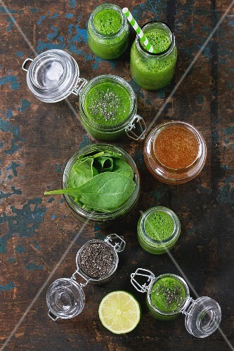 Spinach smoothie in jars served with spinach leaves, chia seeds, honey and lime
