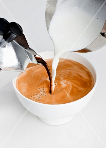 Espresso and milk being poured into a cup