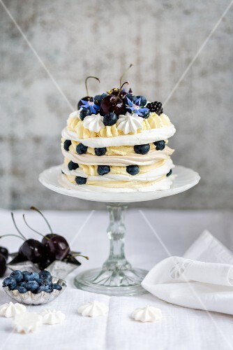 A meringue layer cake with whipped cream, lemon curd and berries on a cake stand