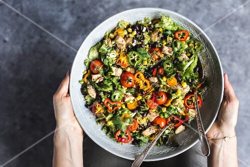 Hands holding a bowl of southwestern chicken salad with avocado dressing