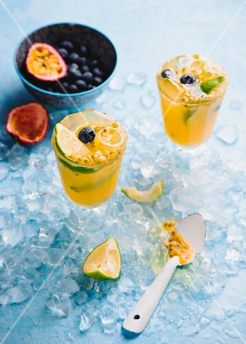 An orange drink with passionfruit, lime and blueberries
