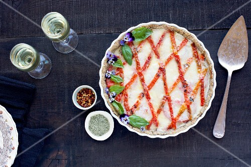 Roasted Red Pepper Fennel Tart with lattice design, fresh basil and edible flowers served with wine