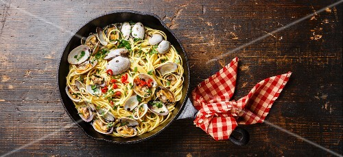 Spaghetti alle Vongole Seafood pasta with clams on black iron pan
