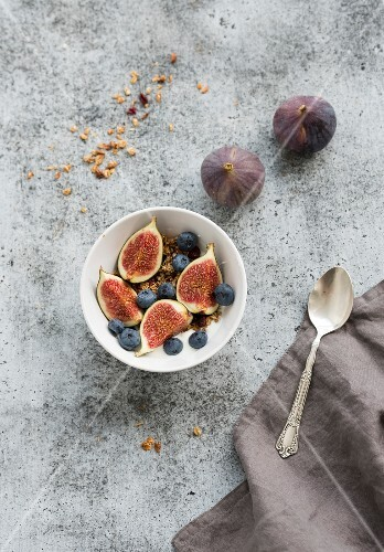Oat granola crumble with fresh figs and blueberrie in white bowl on grunge grey backdrop