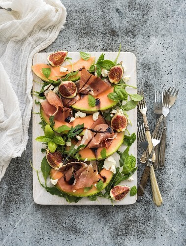 Prosciutto, melon, figs and soft cheese on a white serving board over grunge background