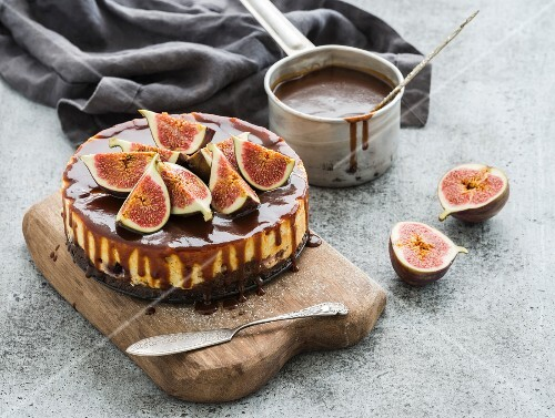 Homemade fig cake with caramel sauce in dipper and fresh figs on wooden board over grey concrete background