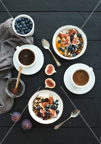 Bowls of oat granola with yogurt, fresh blueberries and figs, cups of coffee and honey