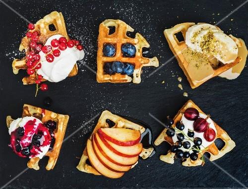 Warm belgian homemade waffles with fresh garden berries, fruit and ice cream on dark slate stone background