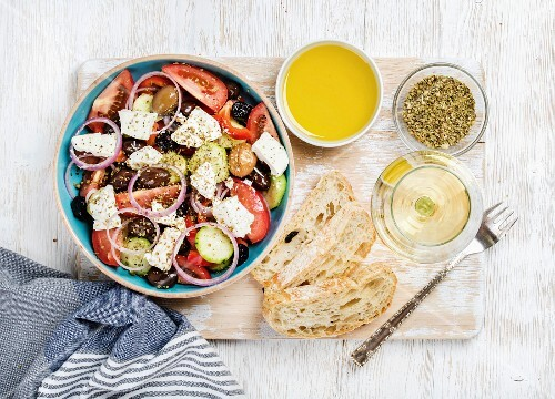 Greek salad with olive oil, bread, oregano and glass of white wine over old white painted wooden board