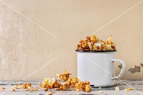 Prepared caramelized sweet popcorn served in vintage white enameled mug