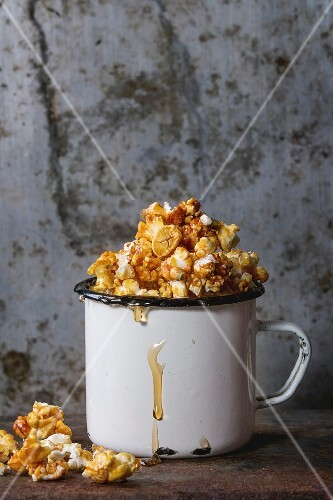 Caramelized sweet popcorn served in vintage enameled white mug with pouring caramel