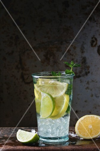 Homemade lemon and lime lemonade, served in glass with ice and fresh mint