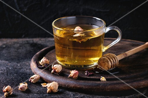 Glass cup of hot herbal tea with dry roses buds, served with honey on honey dipper