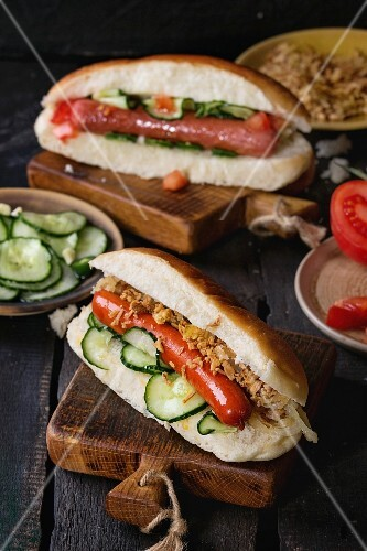 Two of homemade hot dogs with sausage, fried onion, tomatoes and cucumber, served with ingredients