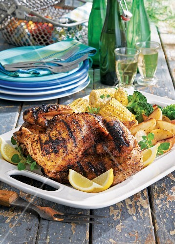 Half a grilled garlic roast chicken with sweetcorn and potato wedges