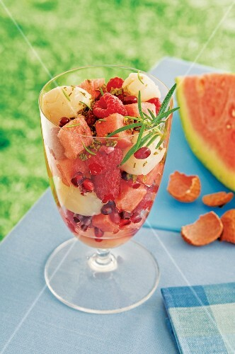 A fruit salad with lychee, raspberries and watermelon on a table outdoors