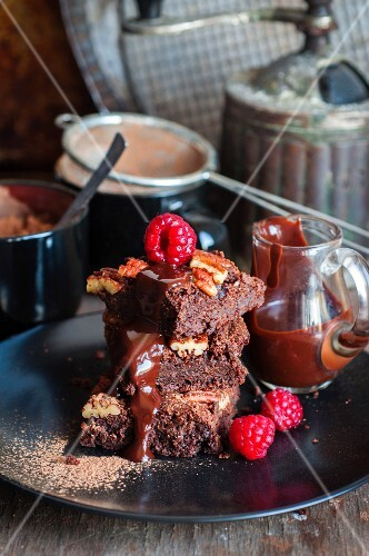 Brownies with pecan nuts, chocolate sauce and raspberries
