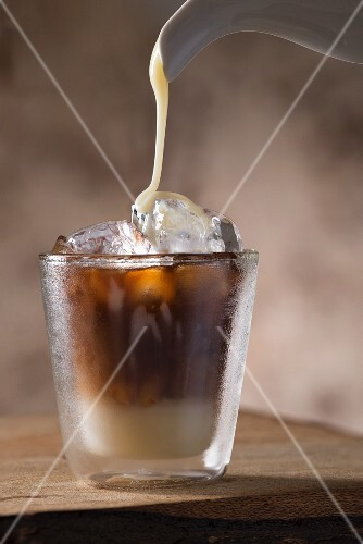 Sweetened condensed milkbeing poured into a glass of Vietnamese iced coffee