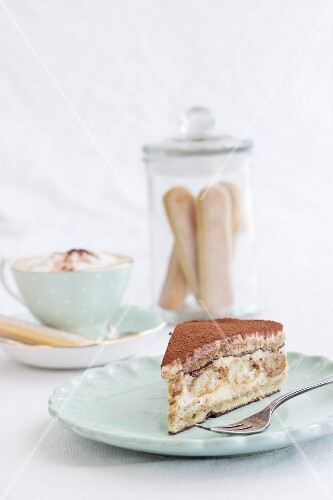 A slice of tiramisu cake and a cappuccino