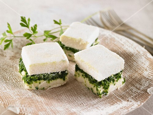 Vegan macadamia nut cheese cubes with spinach and cashew nuts