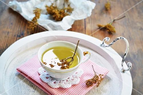Elderflower tea in a teacup on a tray in front of dried elderflower